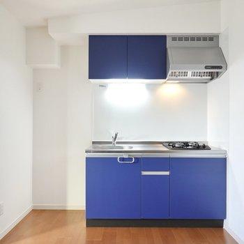 シンプルな空間に映えるブルーのキッチン。冷蔵庫置場は左側に。