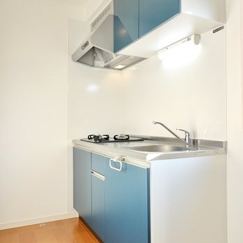 シンプルな空間に映えるブルーグレーのキッチン。冷蔵庫置場は背面側に。