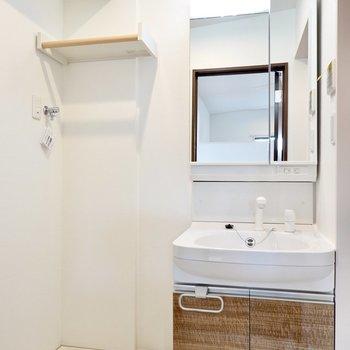 脱衣所の正面には洗面台と洗濯機置場。洗剤などを置ける棚のデザインが素敵……!