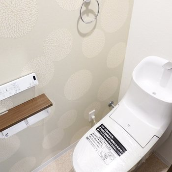 たんぽぽのような植物柄のクロスの横には、ウォシュレット付きのトイレ。スタイリッシュなフォルムで見ているだけでも楽しい!