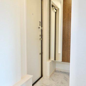 玄関はキッチンのすぐ隣に。奥には姿見付きの靴箱があります。