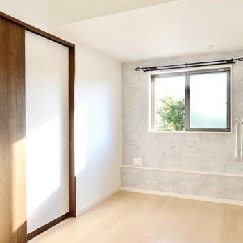 玄関を抜けるとLDK。ナチュラルなインテリアが似合う雰囲気に、窓側のモルタル調のクロスがアクセントに。