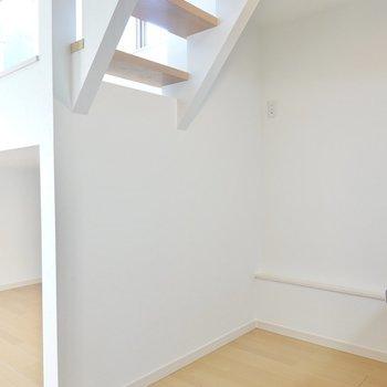 冷蔵庫置場は背面側に。階段下は白と木目のナチュラルなラックを置くと似合いそう!
