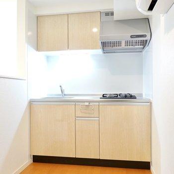 奥にはナチュラルな色味のキッチンがあります。冷蔵庫はエアコンの下に置くことになりそうです。