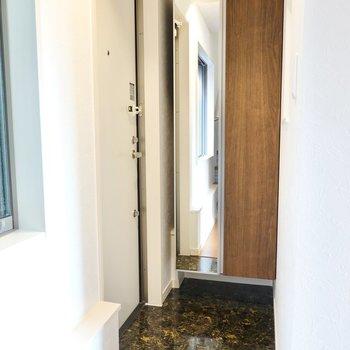 玄関は階段を降りて正面に。奥には姿見付きの靴箱があります。