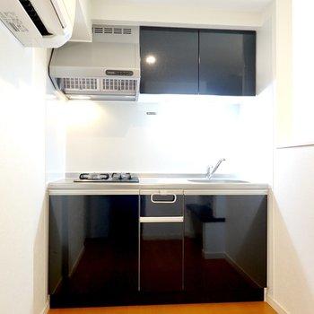 奥にはブラックのキッチンがあります。冷蔵庫はエアコンの下に置くことになりそうです。