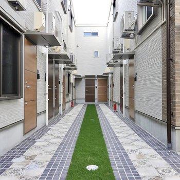 玄関前の共用部は人工芝とタイルが敷かれた空間。宮廷内の中庭のようで、出た瞬間に気持ちが晴れそう◎