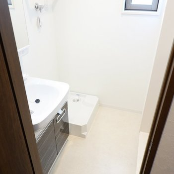 脱衣所に入ると奥に洗濯機置場。洗剤などを置ける棚のデザインが素敵で、脱衣スペースもゆったり。