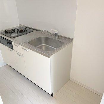 2口コンロにグリルも付いたシステムキッチン。隣には冷蔵庫を置けます。