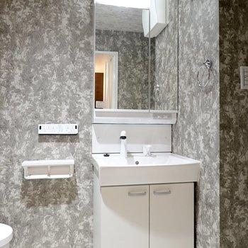 右手には洗面台。鏡の裏が収納になっています。(※写真は4階の同間取り別部屋のものです)