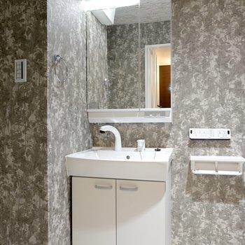 左手には洗面台。鏡の裏が収納になっています。(※写真は2階の反転間取り別部屋のものです)
