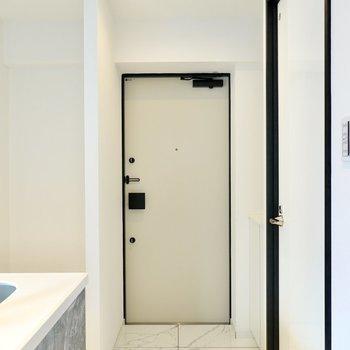 玄関はキッチンの後ろに。タタキもタイルで明るい印象。