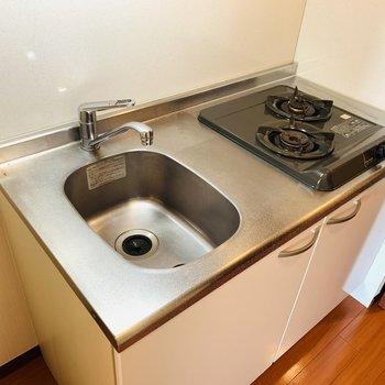 キッチンは二口のガスコンロ。カッティングボードなどを置いて作業台を確保。