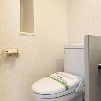 そのお隣にはトイレ。壁にはスマートな収納も。