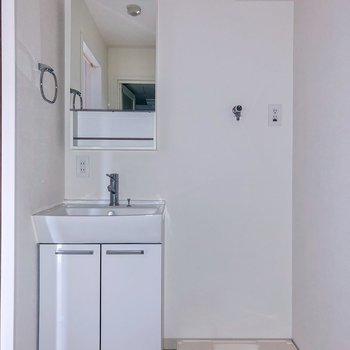 真っ白な洗面台と洗濯機置き場がお隣さん。※写真は3階の同間取り別部屋のものです