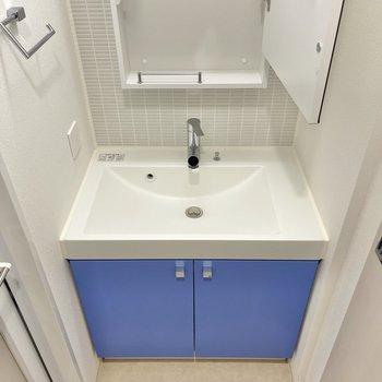 鮮やかな青が印象的な洗面台。鏡の内側は収納になっています。