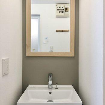 木の枠の鏡がとってもキュート。グレーのアクセントクロスがここにも。