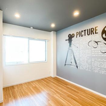 お次は廊下側の洋室へ。すると、投影機が描かれた個性的なアクセントクロスが。