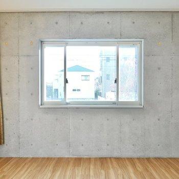 腰高の窓が外の景色を絵画のように切り取る。真ん中がFIX窓で左右が開閉できる珍しいタイプ。
