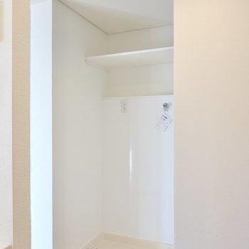 洗濯機置場はキッチンの反対側にあります。洗剤などを置ける棚付きでとっても便利。