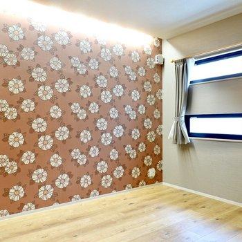 東側の洋室は体感8帖ほど。花柄のアクセントクロスとコーニス照明がデザインホテルのよう。