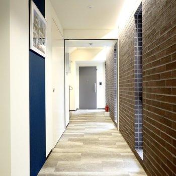 玄関前など共用部はタイルの床にレンガの壁が合わさったこだわりの空間。