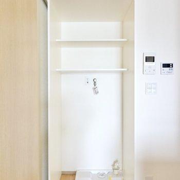 洗濯機置場はキッチンの後ろ側に。棚付きで、突っ張り棒を使えば目隠しカーテンも降ろせます。