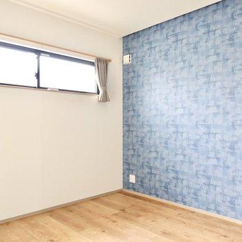 LDK側の洋室は6帖ほどの広さ。青いチェック柄のアクセントクロスが独特。