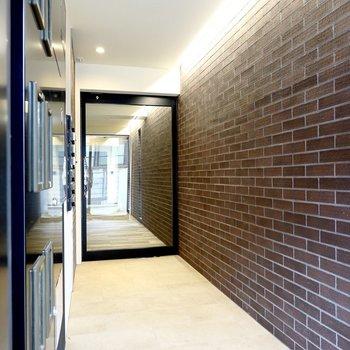 エントランスでは光に照らされたレンガの壁がお出迎え。もちろんオートロックです。