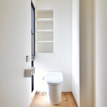 右側にはタンクレストイレ。横からの光が陰影を生み、アートのような非日常感のある空間に。