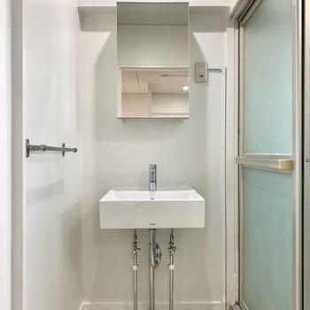 扉を開けて正面には洗面台!鏡の後ろは洗面台になっています。(※写真は6階反転間取り別部屋のものです)