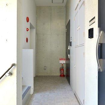 お部屋はエレベーターを降りて正面。共用部にもコンクリートの躯体が表れています。