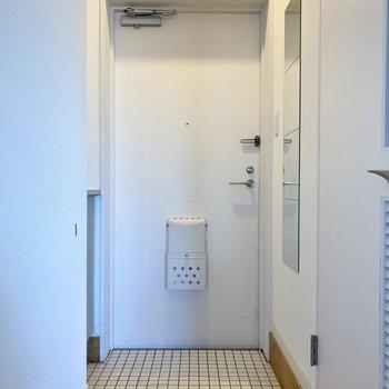 玄関は白タイルでさわやかに。