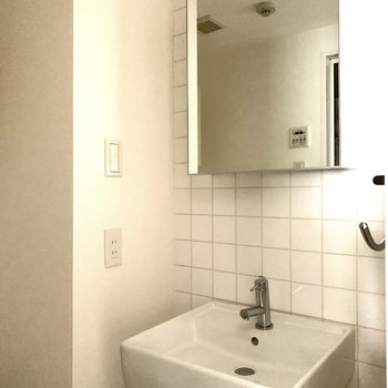 洗面所もキッチンとお揃いのタイルが素敵。シンプルでスタイリッシュな空間です。(※写真は9階の同間取り別部屋のものです)