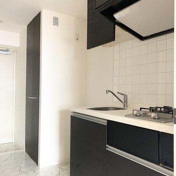 キッチンは廊下に。奥の扉の中は洗濯機置場です。(※写真は9階の同間取り別部屋のものです)