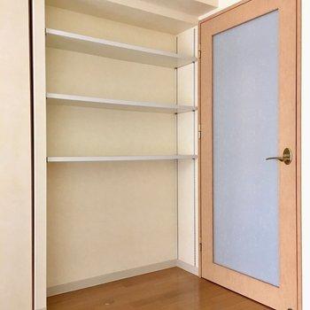リビングの収納棚には小物や本を置きたいな。(※写真は8階の反転間取り別部屋、モデルルームのものです)