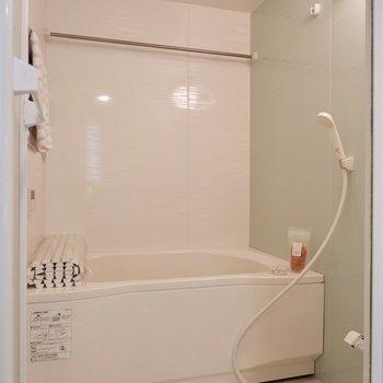 くすみブルーの壁材がアクセントの浴室。乾燥機付きですよ。