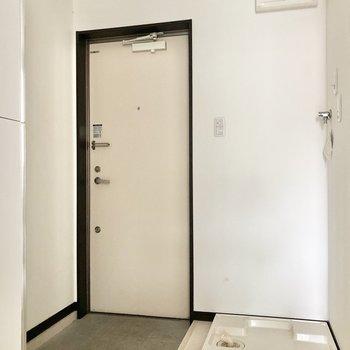 洗濯機置場は玄関横に。玄関土間はコンパクトです。※写真は通電前・一部フラッシュを使用して撮影しています