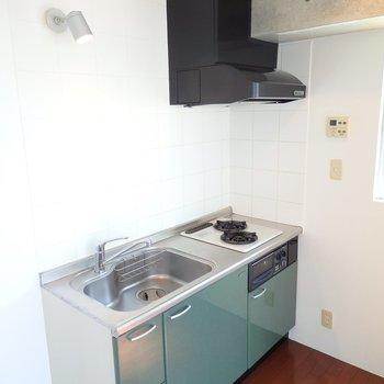 キッチンはスモーキーなグリーン。コンロは2口。(※写真は8階の同間取り別部屋のものです)