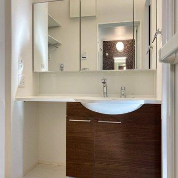 鏡の大きな洗面台。左下にはランドリーボックスなど入れておくと便利そう。