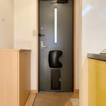 玄関はタタキ部分が台形になった面白いデザイン。洗濯機置場も玄関前にあります。