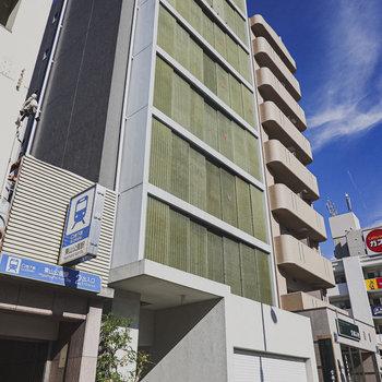 駅の2番出口すぐ横のシンプルな外観のマンション。