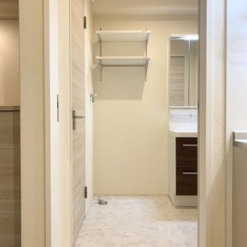 サニタリーはキッチンのお隣に。洗濯機置場の上には便利な棚付き。(※写真は2階の同間取り別部屋のものです)