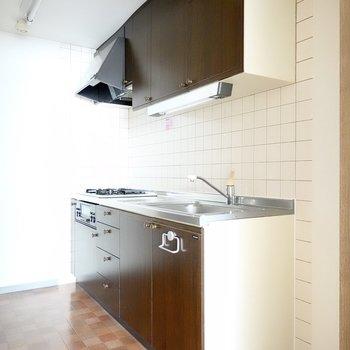 収納たっぷりのキッチンは床の色に合わせたパネル。冷蔵庫置き場は右側に。(※写真は3階同間取り別部屋のものです)