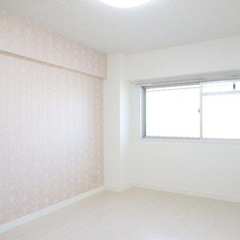 廊下側の洋室も7帖。薄いピンクのアクセントクロスが柔らかい雰囲気。