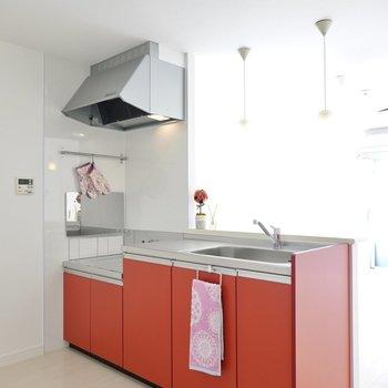 赤いキッチンが真っ白な空間の差し色に。吊り戸棚が無いので開放感も!