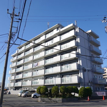 郊外の開けた土地にどーんと構える7階建てマンション。