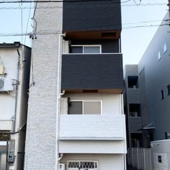 細長い3階建てのアパートです。※前回募集時の写真です。