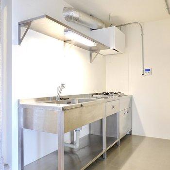 ステンレス製のキッチンで料理の時間も楽しく。上部の棚で魅せる収納も楽しめます。