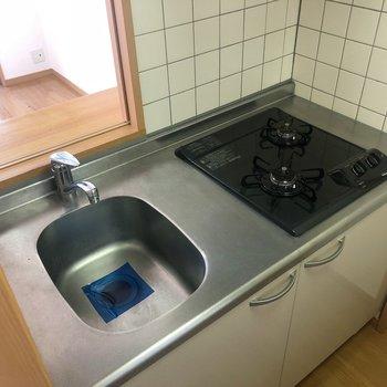 キッチンは必要最低限。冷蔵庫はコンロの後ろにね。(※写真は13階の同間取り別部屋のものです)